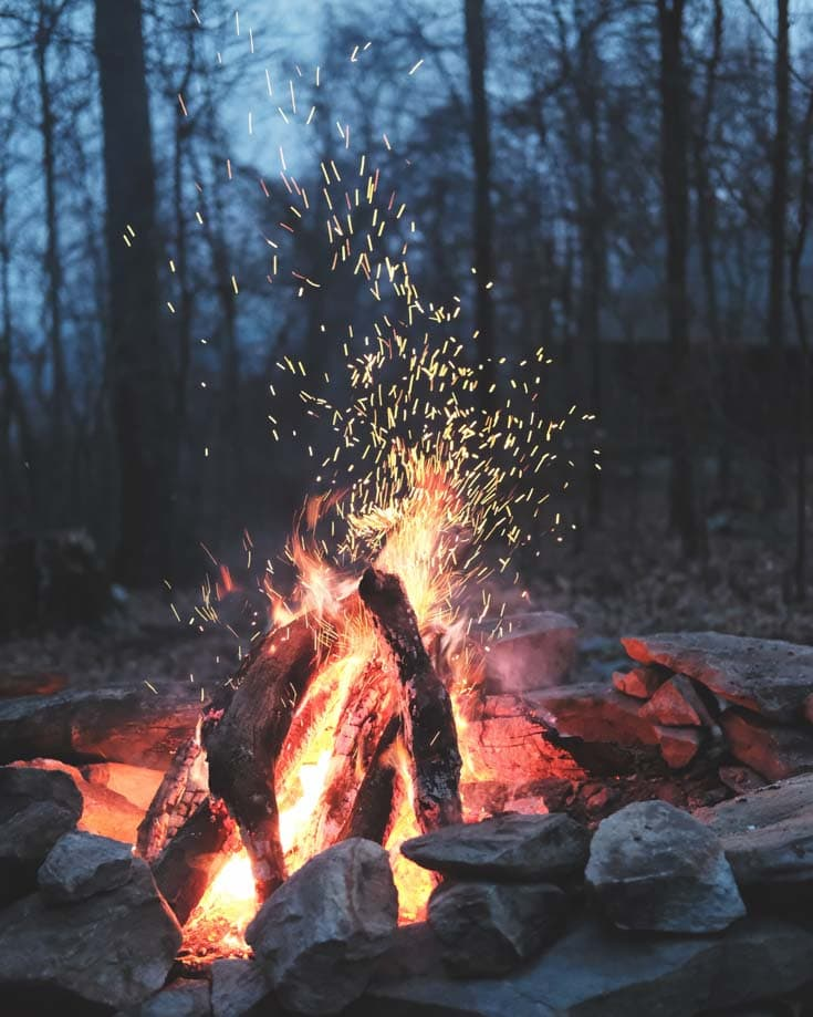 A campfire with sparks floating up in a forest