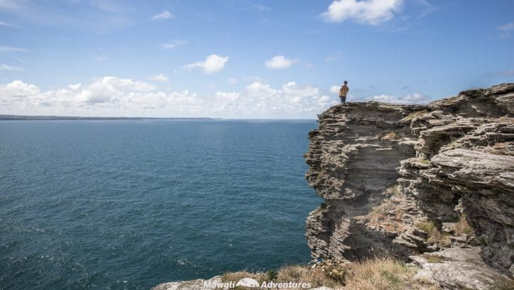 A person standing on the cliff tops overlooking the sea from Tintagel