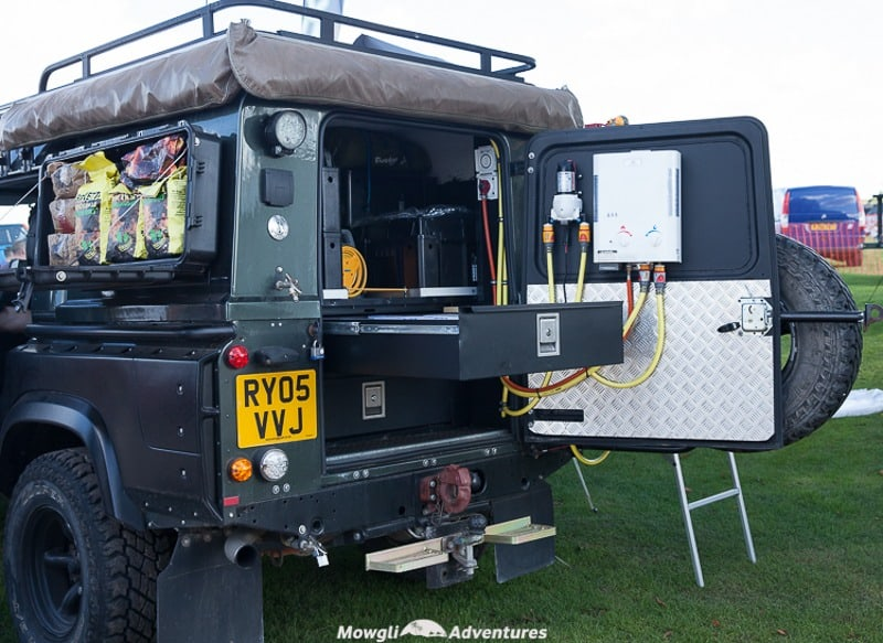 An organised fit out of a land rovers with storage and an outdoor shower
