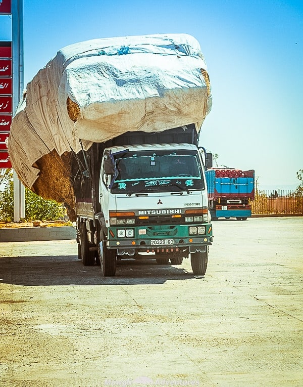 A lorry in Morocco heavily overladen with hay bales falling to one side