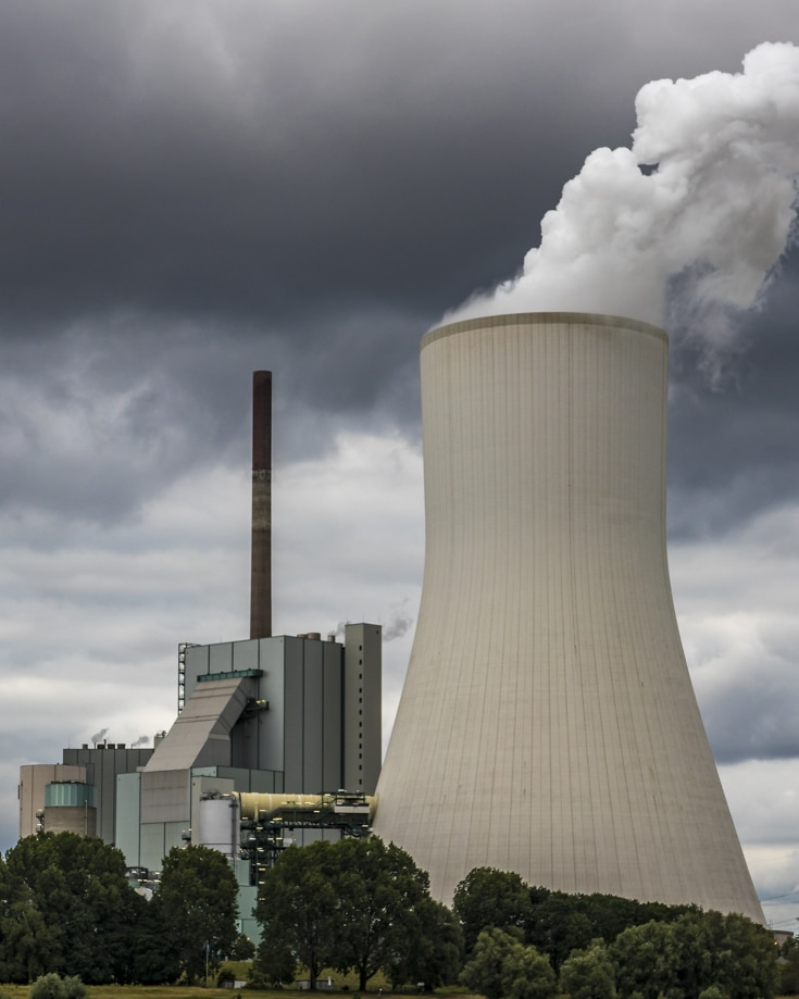 Smoke billowing from an electricity cooling plant chimney