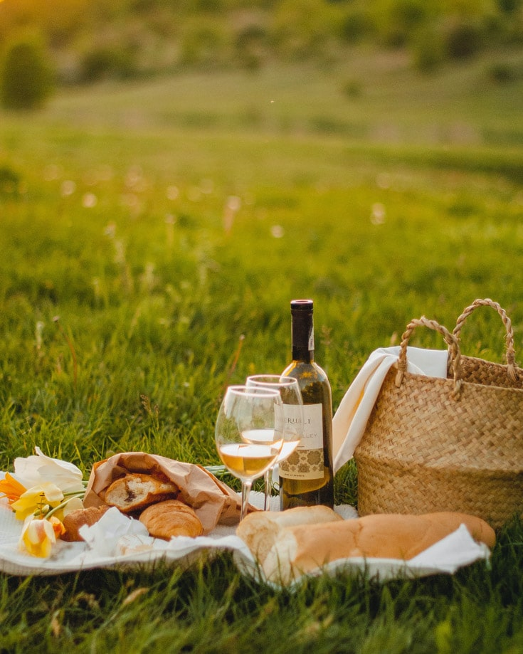 Picnic hamper with wine on a grass lawn in Tintagel