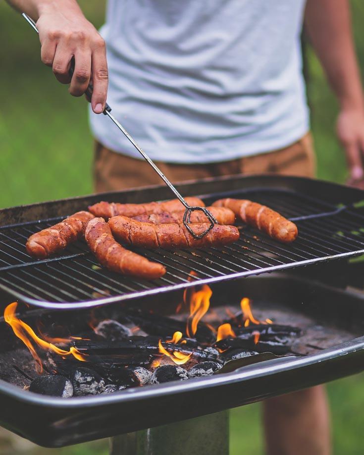 A camper grilling sausages