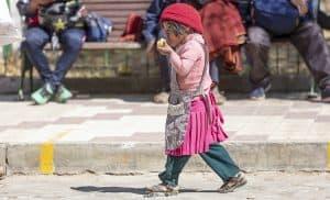 Tarabuco Sunday market - child eating fruit
