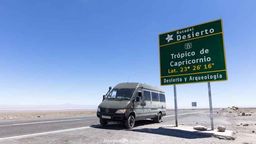 A Mercedes Sprinter campervan conversion beside the Tropic of Capricorn sign in Chile's Atacama desert