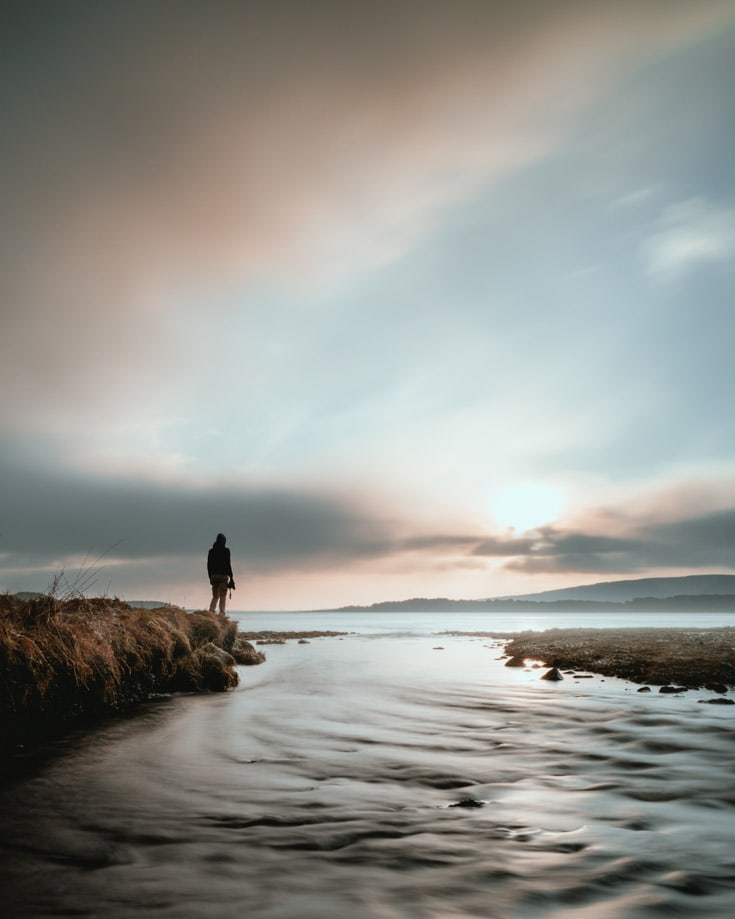 A lone person standing by the coast in Scotalnd