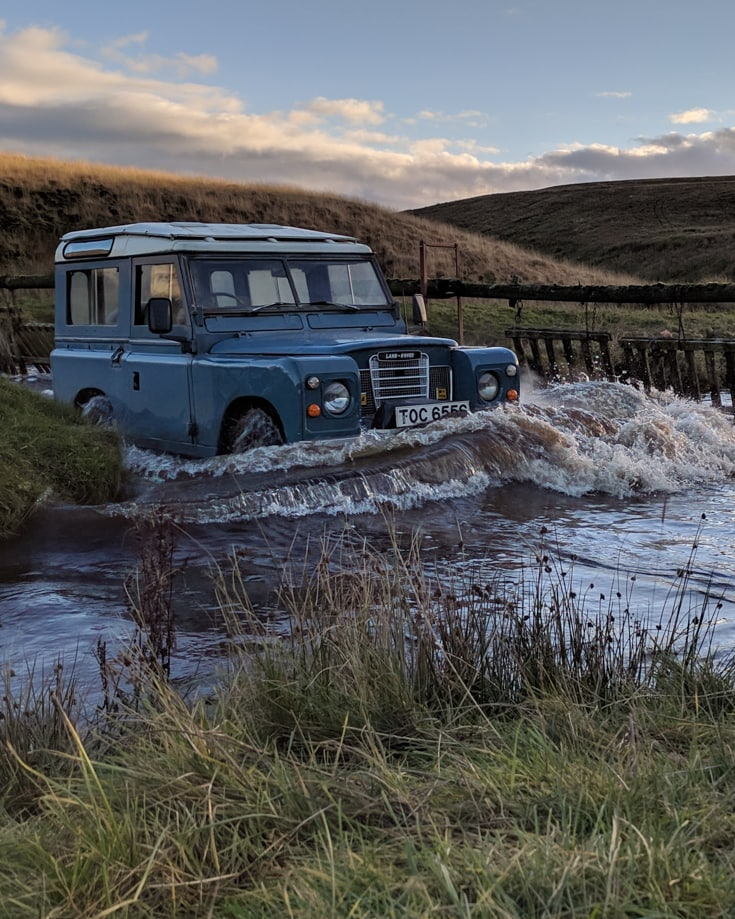 A series 1 Land Rover driving across a river creating a bow wave in front of it