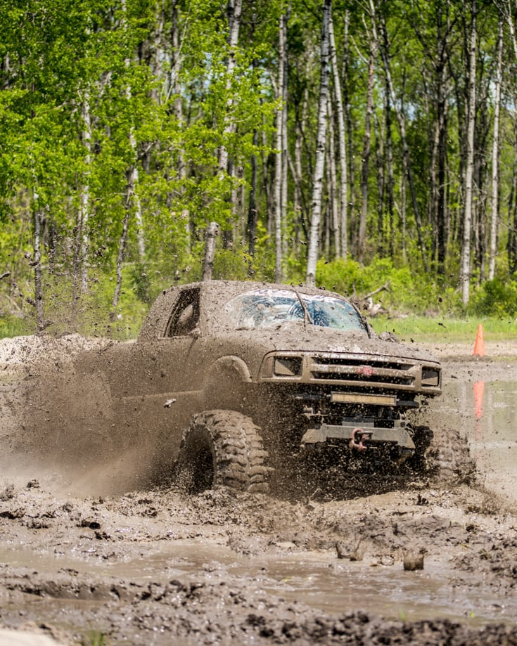 A mud covered 4x4 overland vehicle driving fast through slippery deep mud