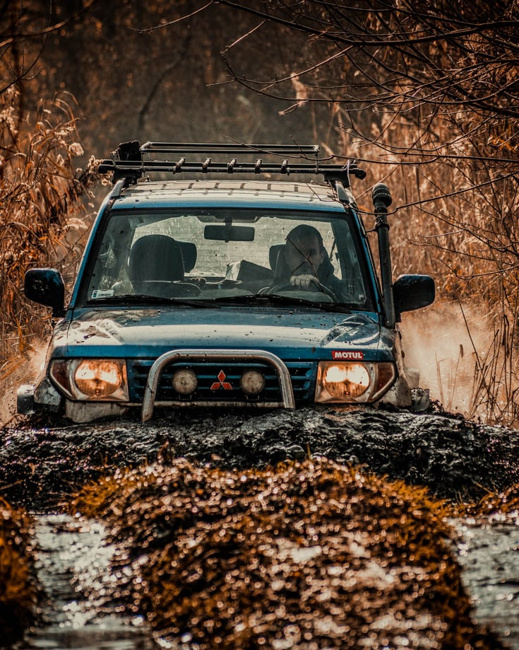 A 4x4 overland vehicle driving through deep mud and water on a country lane