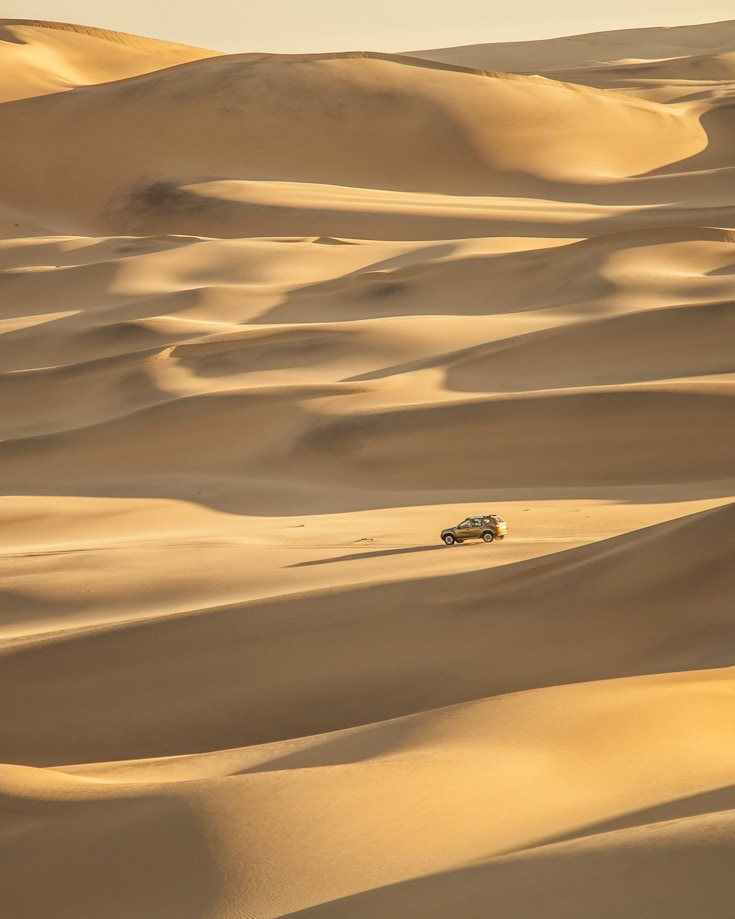 An overland build vehicle driving the the desert is dwarfed by surrounding sand dunes