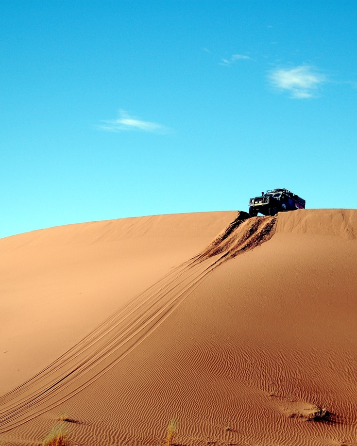 Overland vehicle waiting to drive over a steep high sand dune