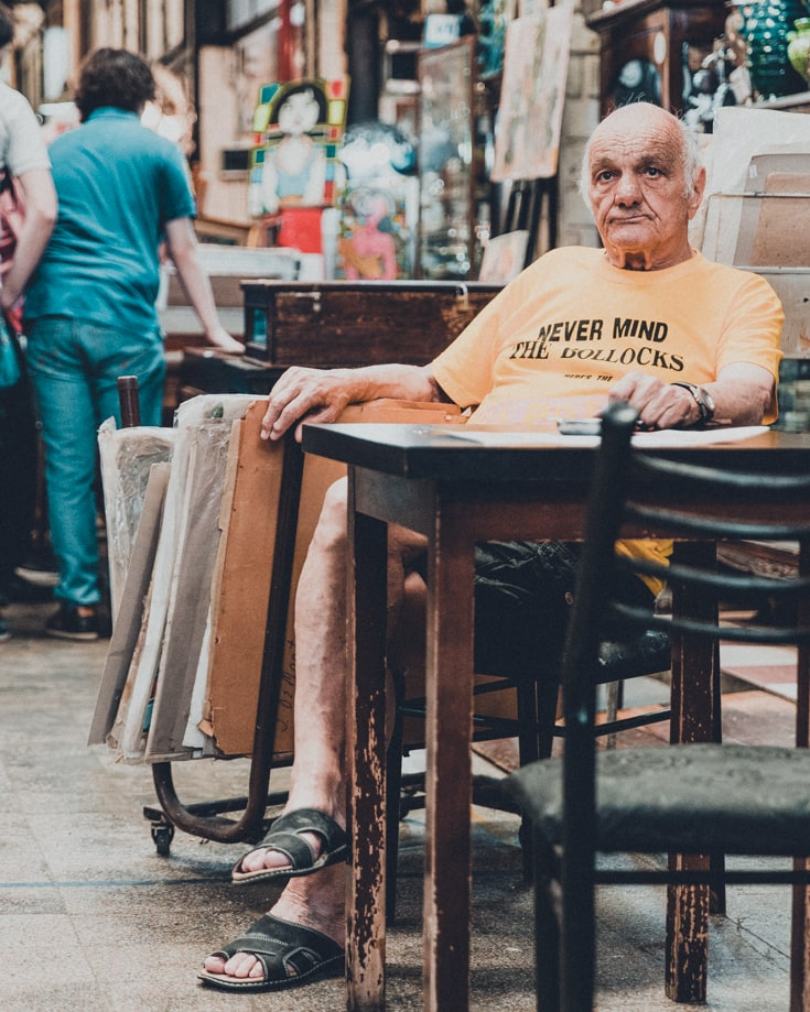 A man sitting at a table watching the world go by in San Telmo market