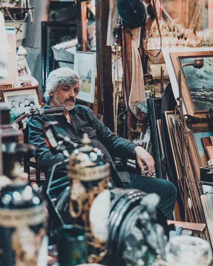 An antiques stall owner waiting for customers in Mercado de San Telmo