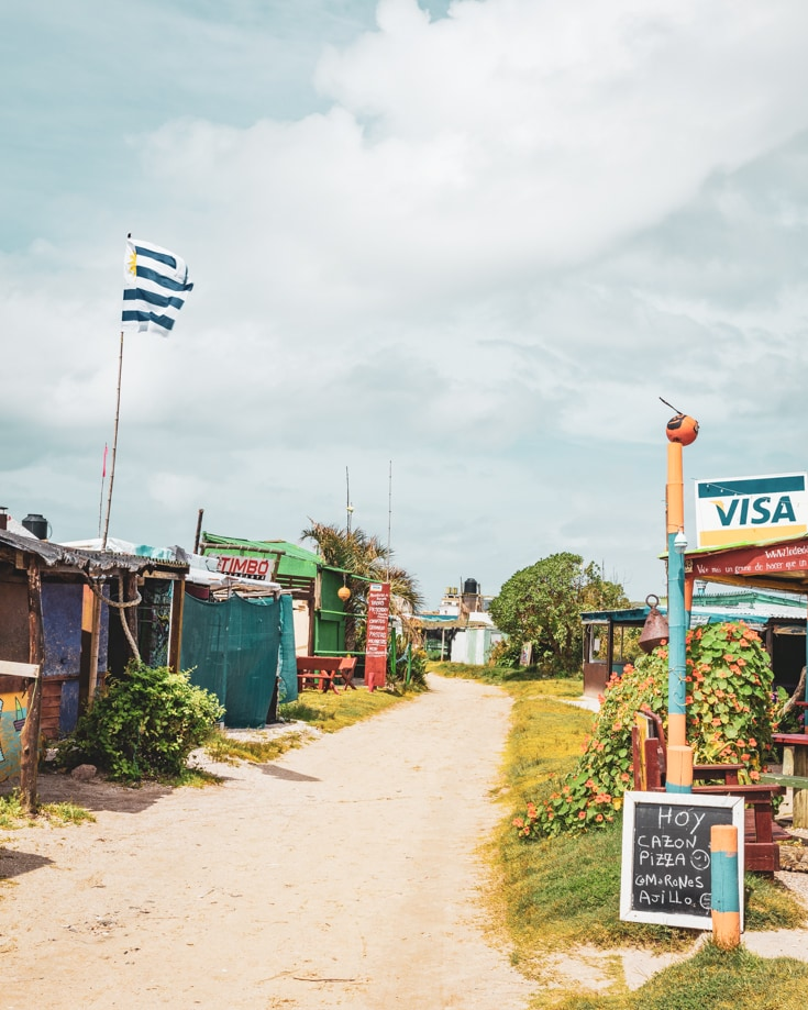 Sandy tracks in Cabo Polonio with the Uruguayan flag flying and a visa sign outside a bar