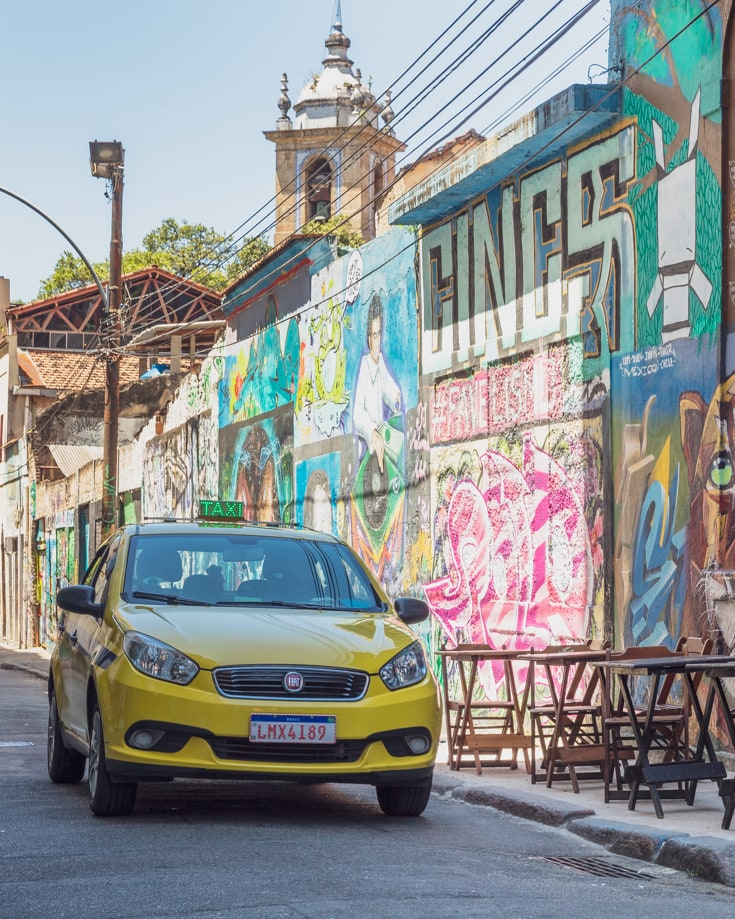 A taxi driving through the graffiti painted streets of Rio de Janeiro