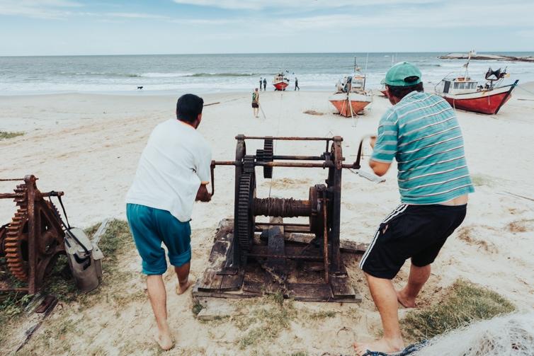 2 men manually winching boats ashore onPlay de los Pescadores, Punta del Diablo Uruguay