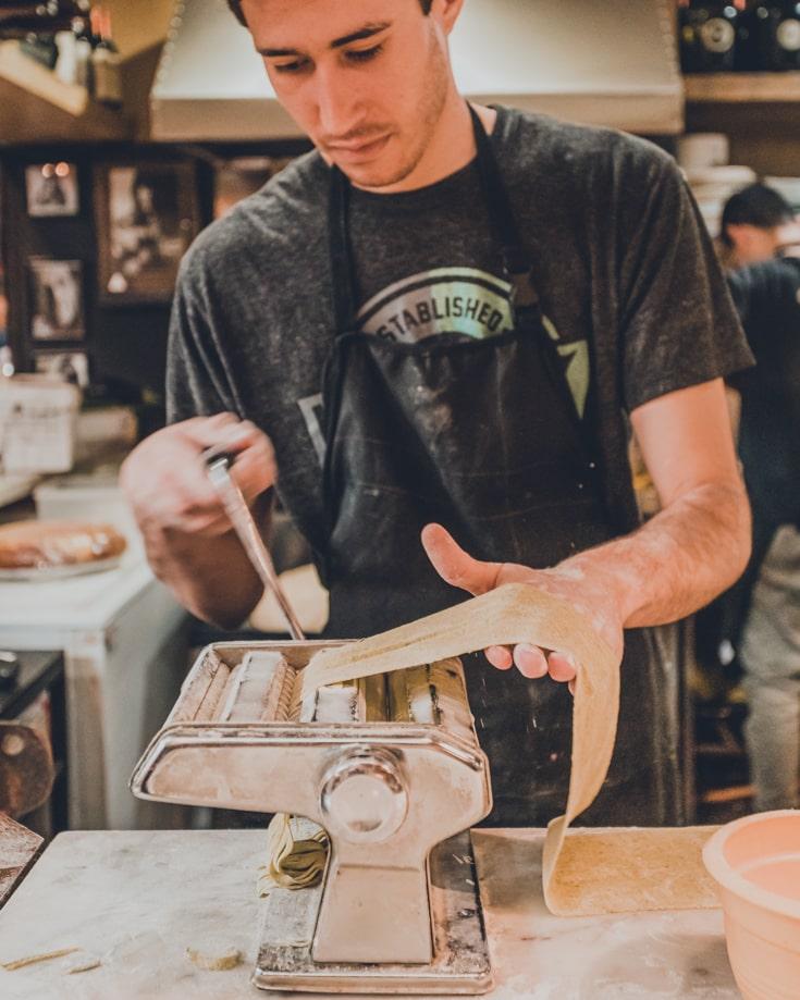A man using a pasta machine to make fresh pasta in Mercado de San Telmo Buenos Aires