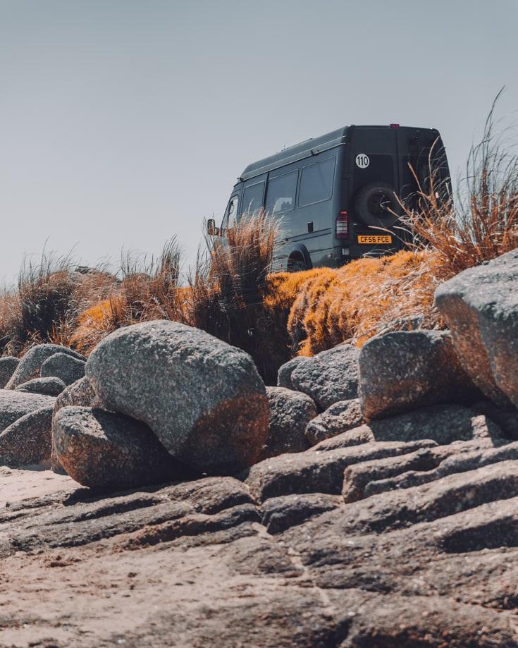 Sprinter camper van free camping on a rocky outcrop in Punta del Diablo Uruguay