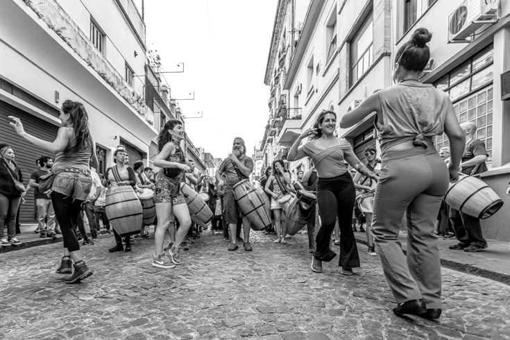 dancers leading a Candombe tripue through cobbled streets