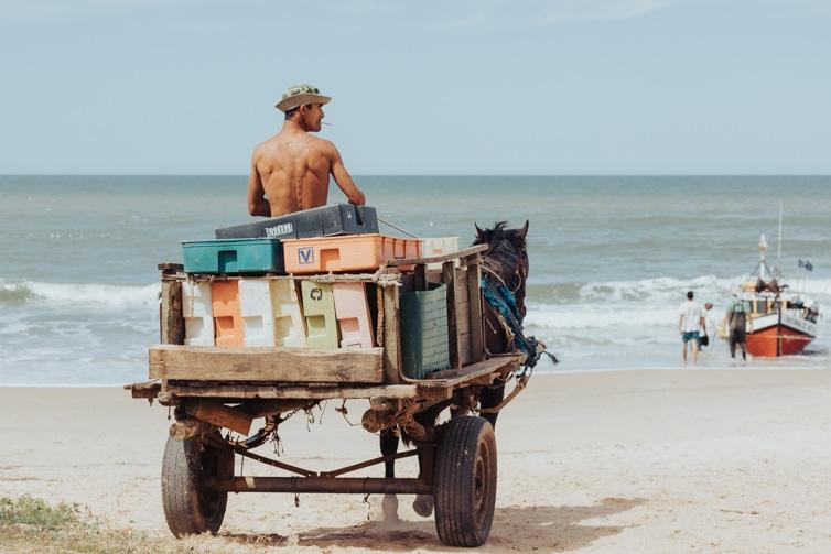 horse drawn cart arrive at Playa del los Pescadores, the driver smoking a cigarette.