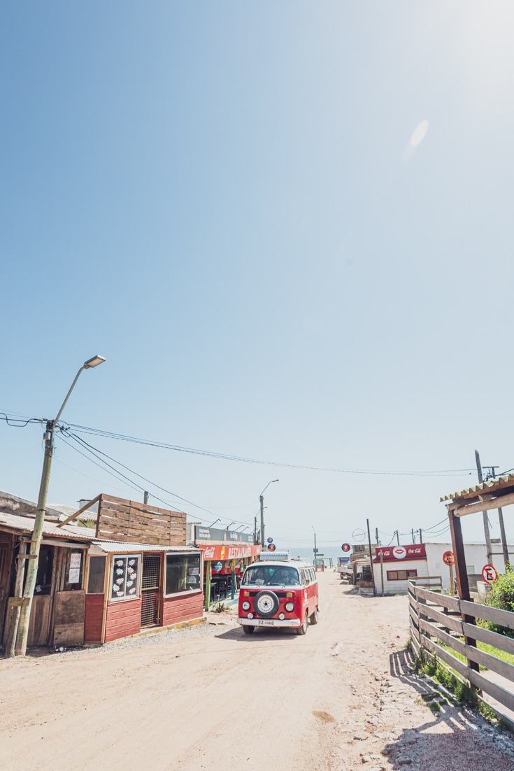 A red VW combi driving through the sandy roads of Punta del Diablo at the end of the summer season