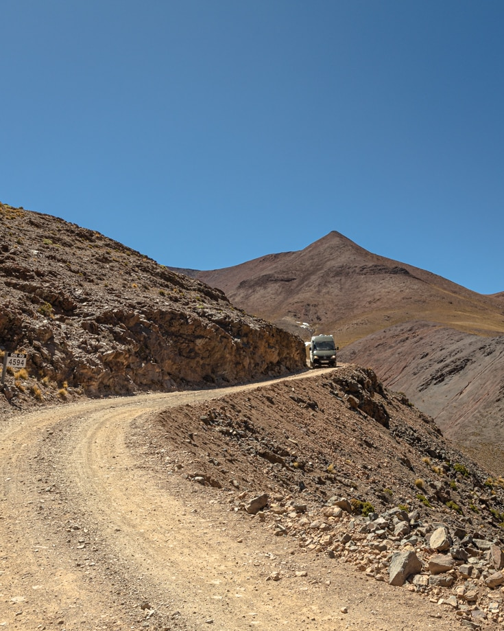A campervan coming round a corner on Abra del Acay on narrow track and steep cliff