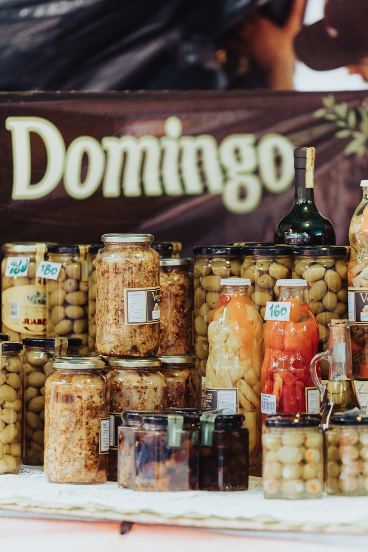 Artisanal jars of pickles for sale at Mataderos Market with a Domingo sign Sunday