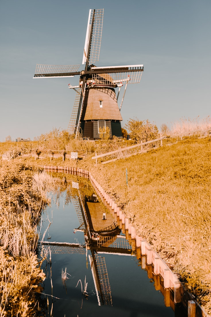 A lone windmill and its reflection in a canal in Haarlem Holland