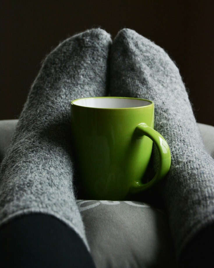 A pair of feet with grey socks hugging a green mug