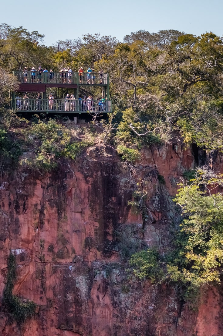 One of the viewing platforms with visitors looking into a sinkhole in Brazil's Buraco das Araras