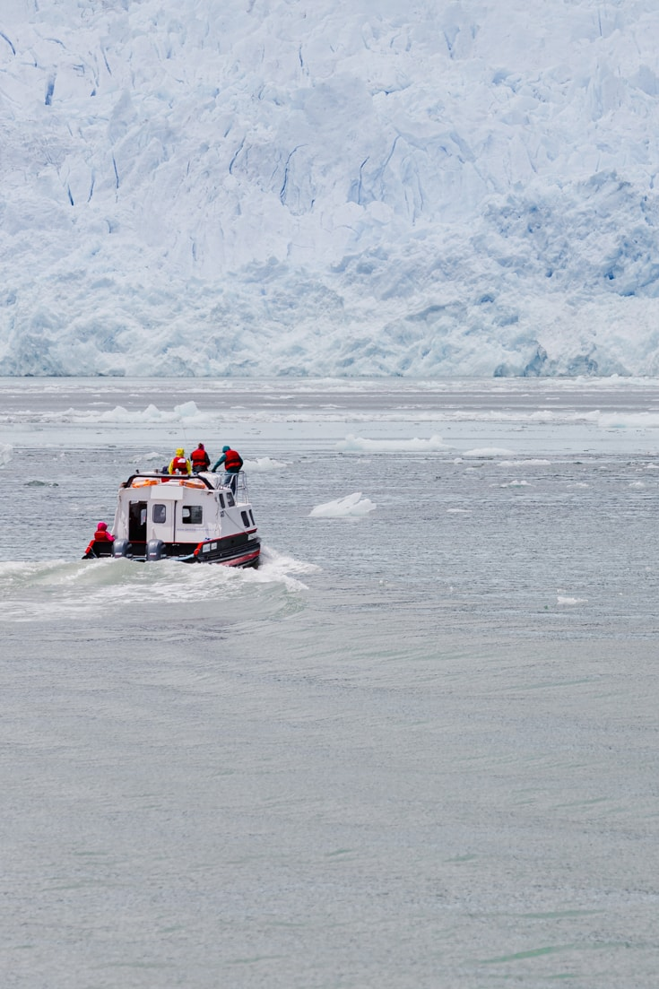 A small tour boat with a a few passengers sails towards the face of a glacier through brash ice