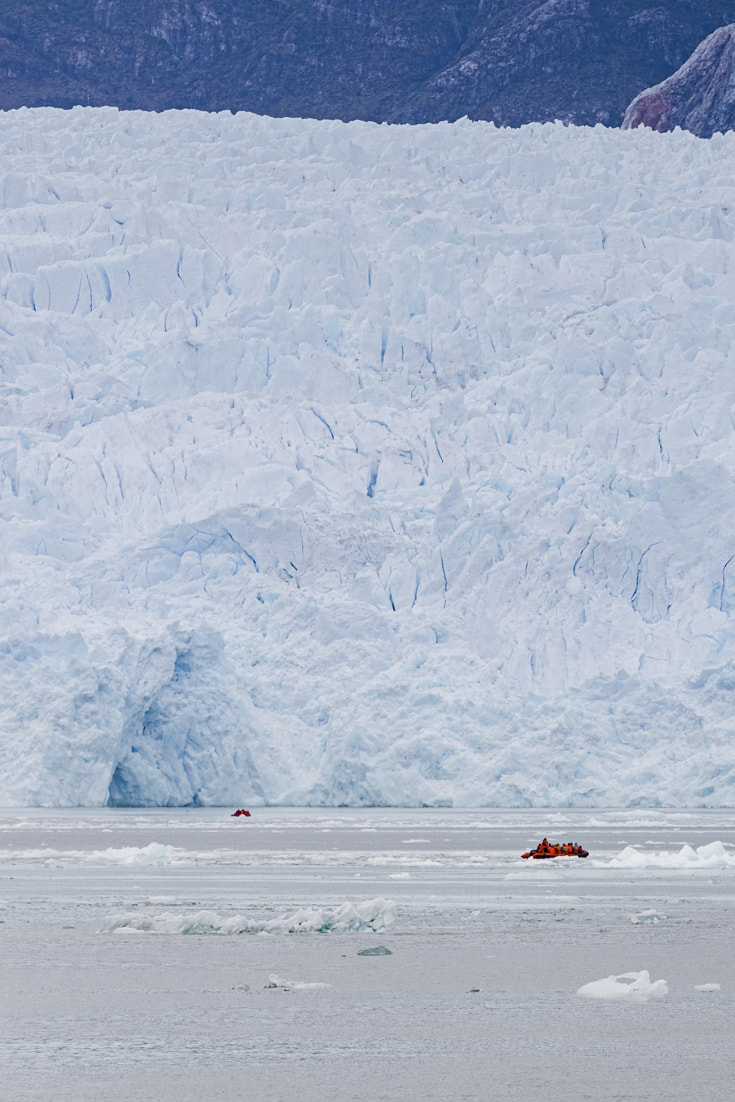 2 zodiacs full of passengers are dwarfed by the massive blue walls of San Rafael glacier in Patagonia's northern Ice Cap