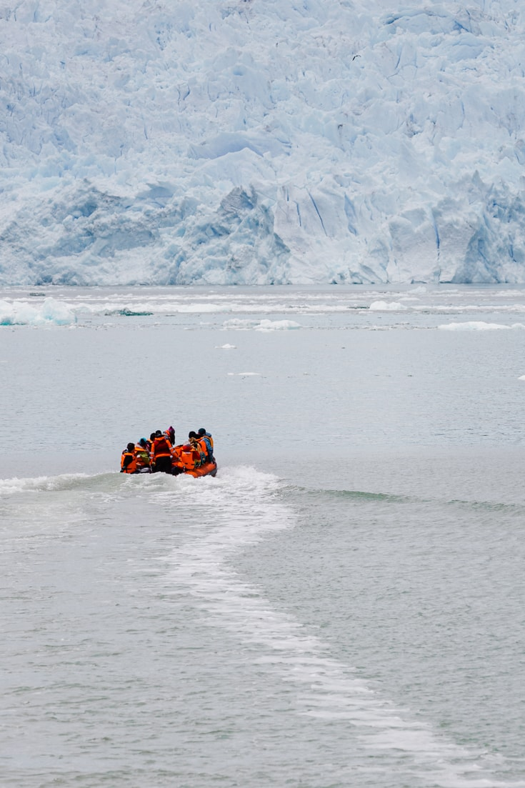 Zodiac with passengers sailing towards the blue face of San Rafael Glacier