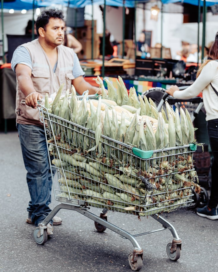 man selling corn on the cob from a shopping trolley in the market Argentina
