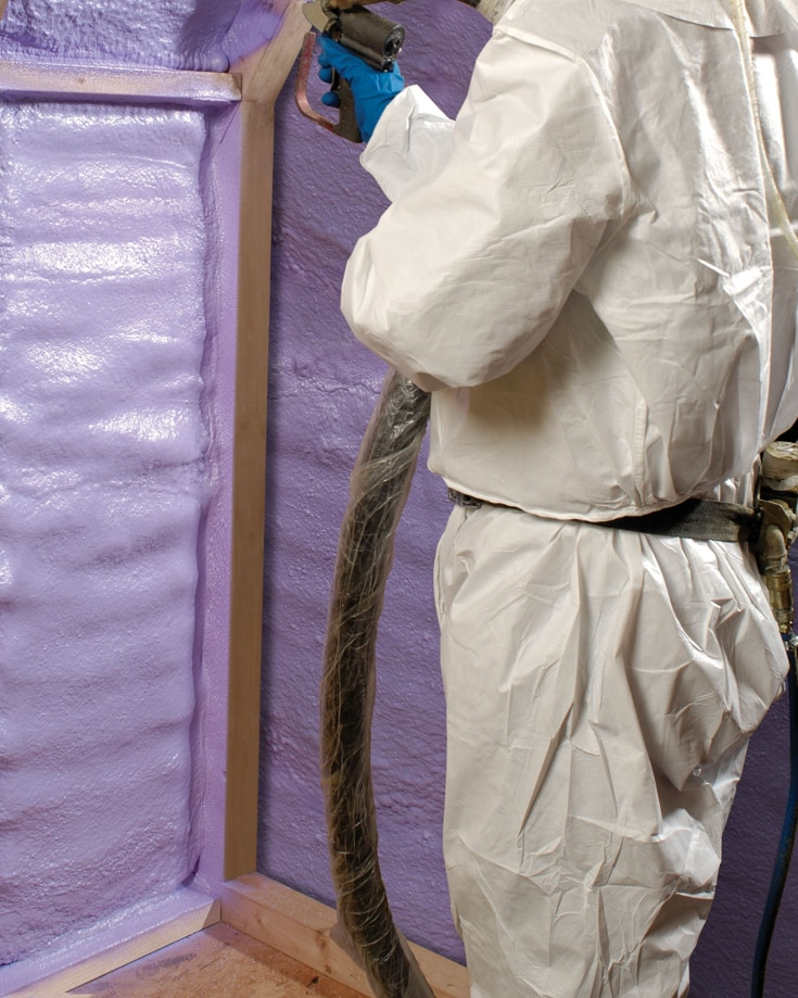 A person in white overalls applying spray foam insulation