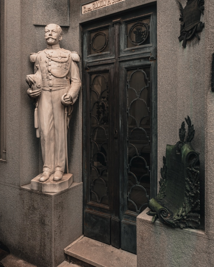 A statue of someone on a mausoleum in La Recoleta Cemetery Buenos Aires