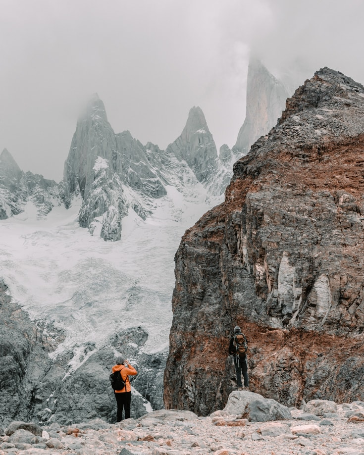 A couple hiking in Patagonia and looking up at a glacier and mountain peaks shrouded in cloud