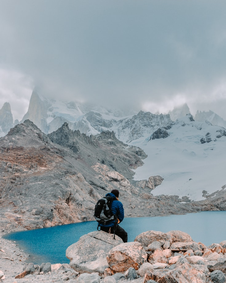 a hiker sitting on a boulder at the top of Mount Fitz Roy hike with a lake in the foreground