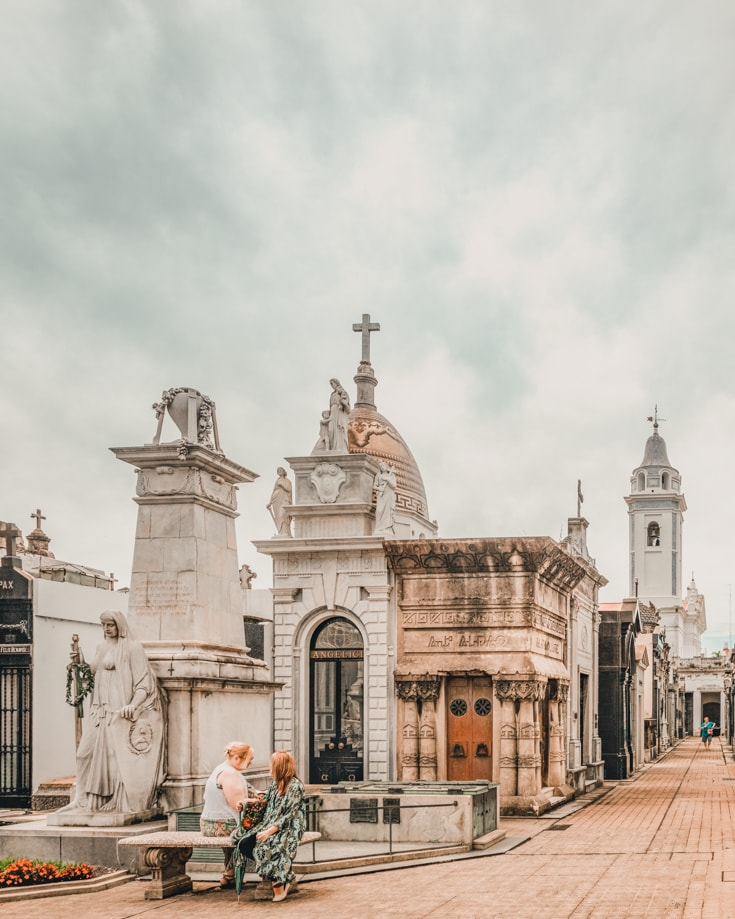 People sitting on a bench in Recoleta cemetery Buenos Aires