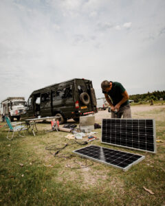A man fitting solar panels to a Sprinter campervan conversion