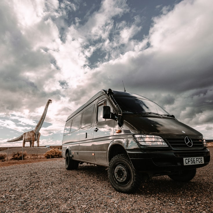A dinosaur staue behind a shiny camper van