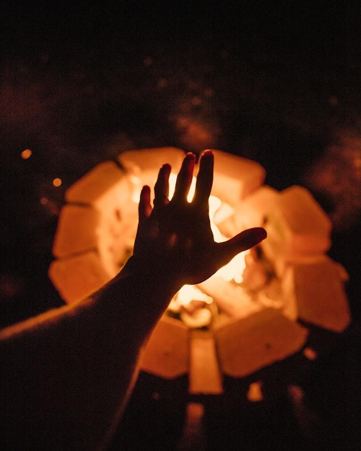 A hand warming itself over a fire