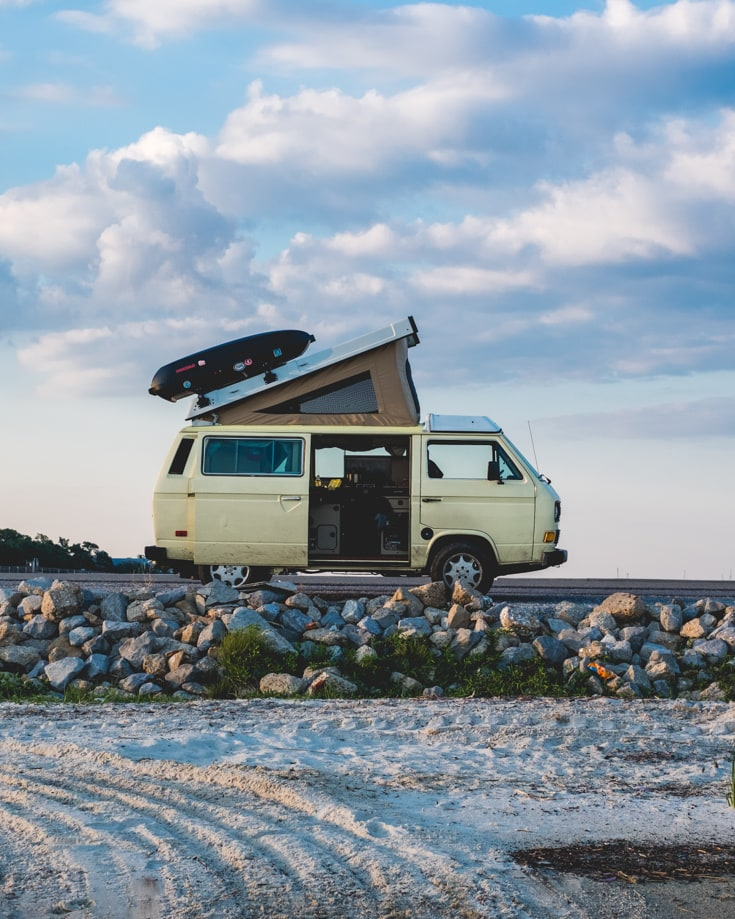 a small campervan with the doors open on the coast