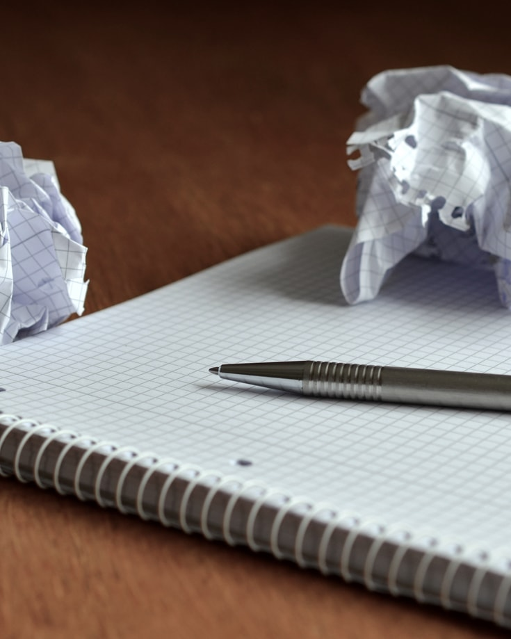 A pen and paper and some crumpled paper
