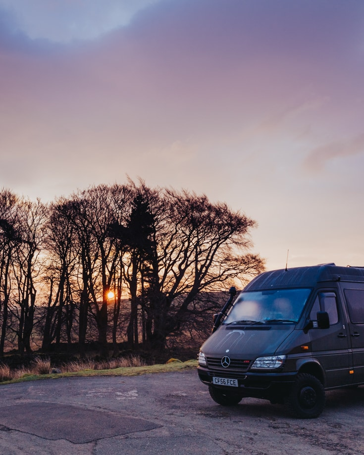 A camper van parked for the night beside trees at sunset.