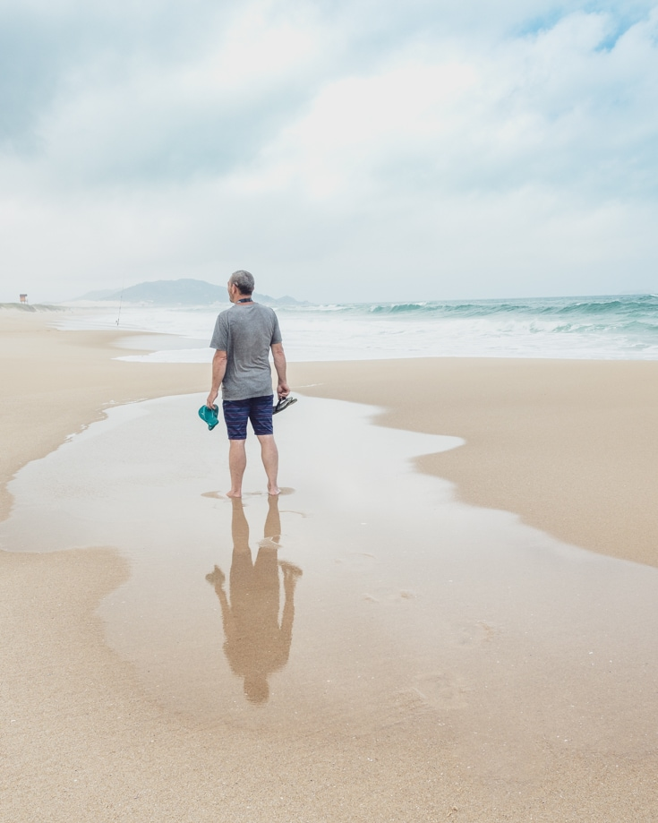 A man standing barefoot on a beach