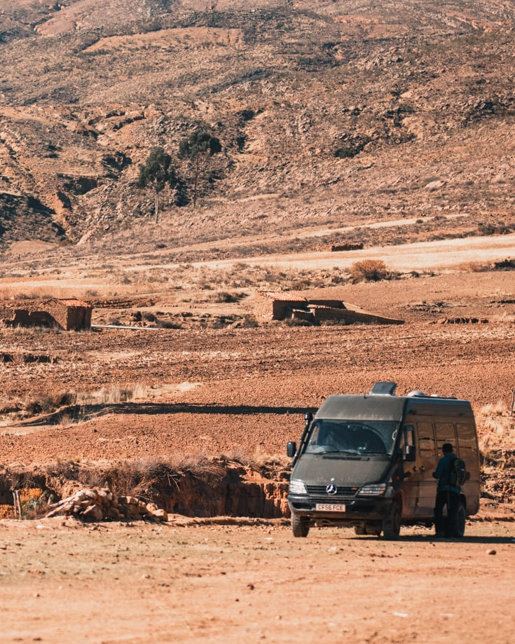 Sprinter van in rocky desert with open doors and roof vent open