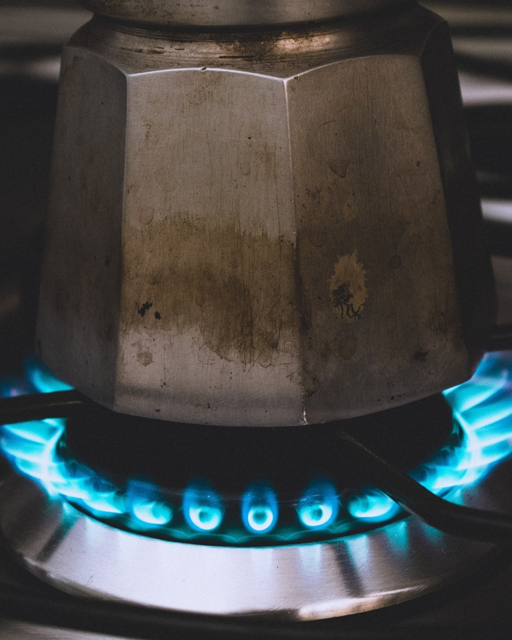 A coffeepot warming on a gas flame