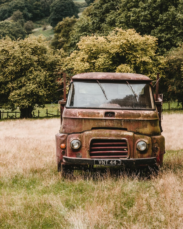 Old rusty campervan abandoned in a grassy field