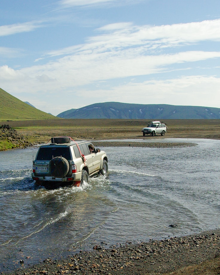 An overland vehicle with a spare wheel on the roof and the back door crossing a river crossing towards another waiting vehicle